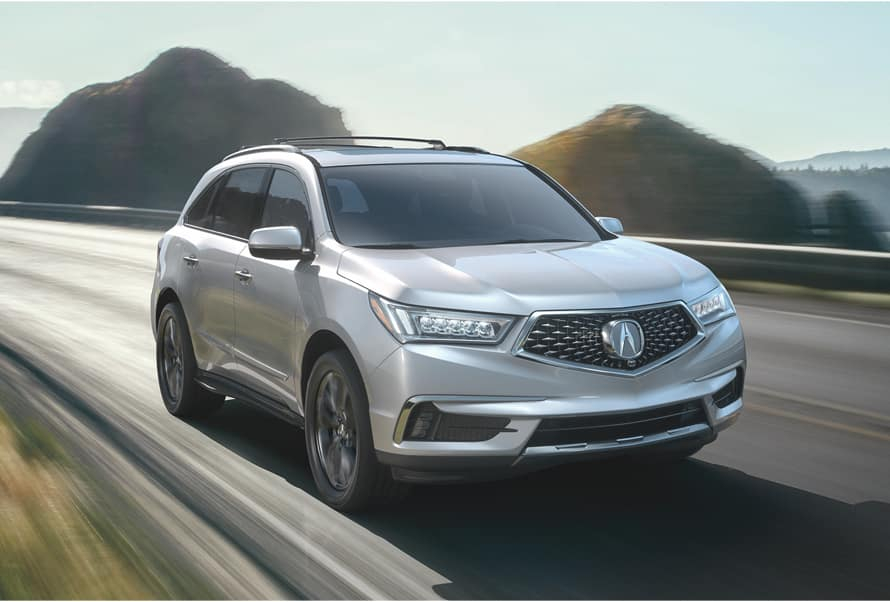 Acura Model Image - Silver MDX driving on a road