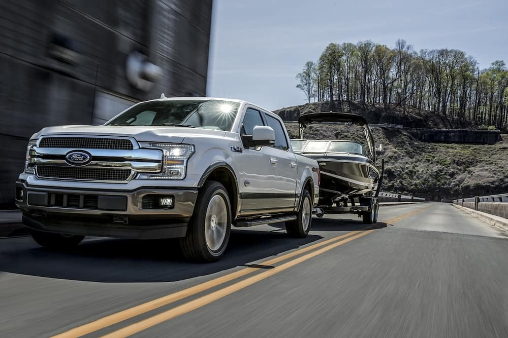 2020 Ford F-150 King Ranch towing a boat on a paved road