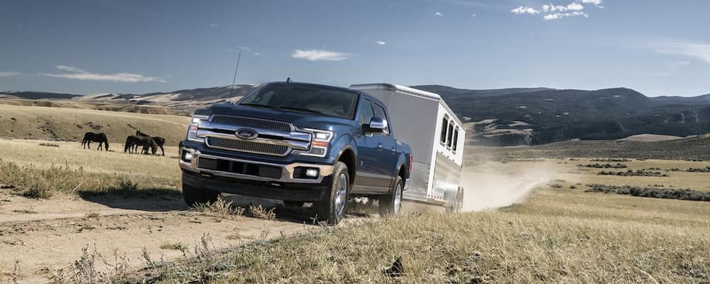 2020 Ford F-150 King Range towing a trailer on a dirt road