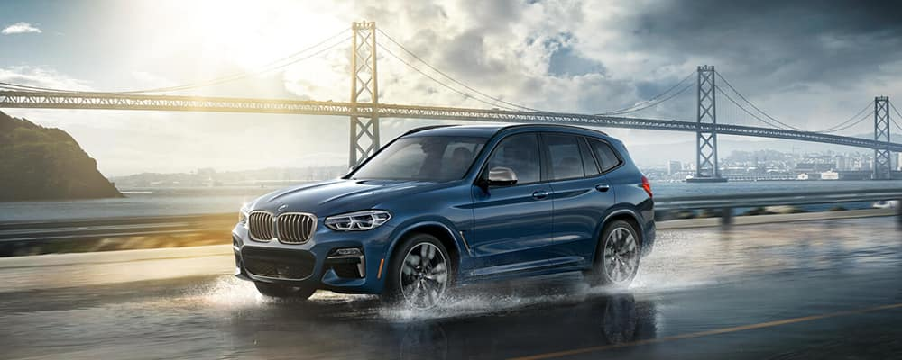 A BMW X3 M40i drives along a damp road in front of a long suspension bridge