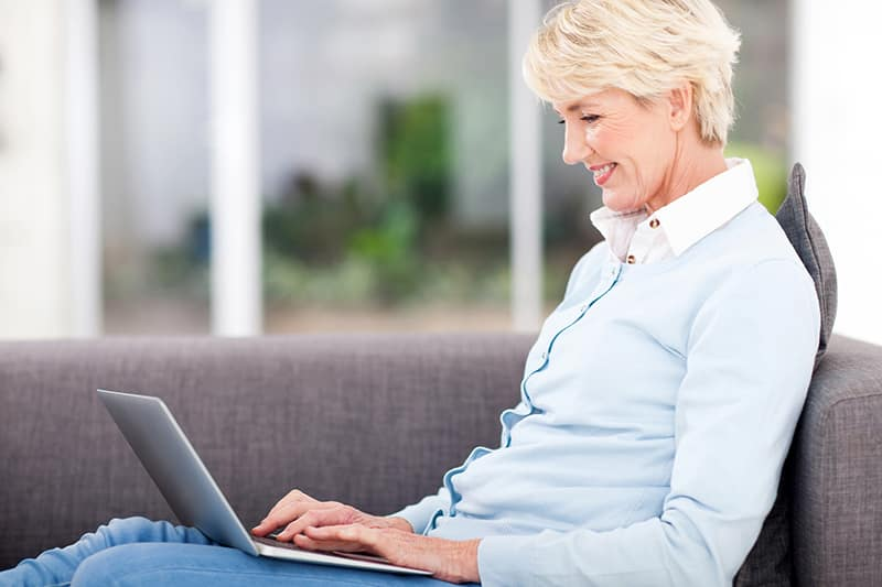 happy elderly woman using laptop computer at home