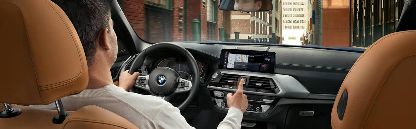 A man holding the steering wheel inside a new BMW
