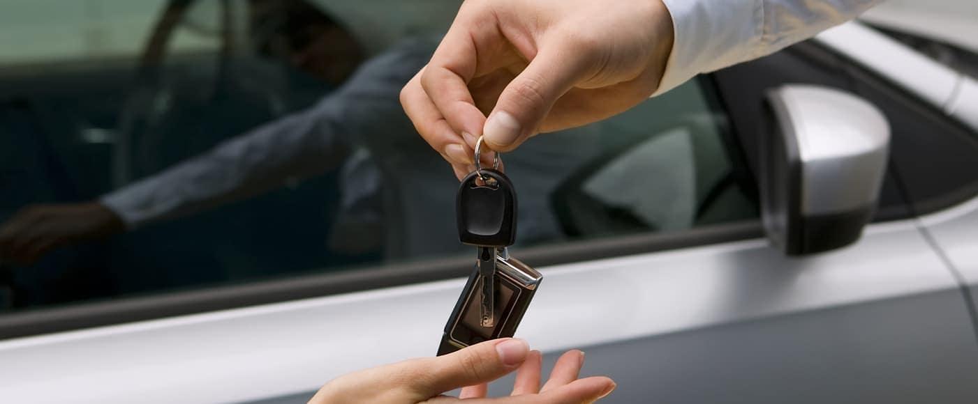 salesman passing over new car key