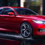 Red Honda Accord driving in rain at night