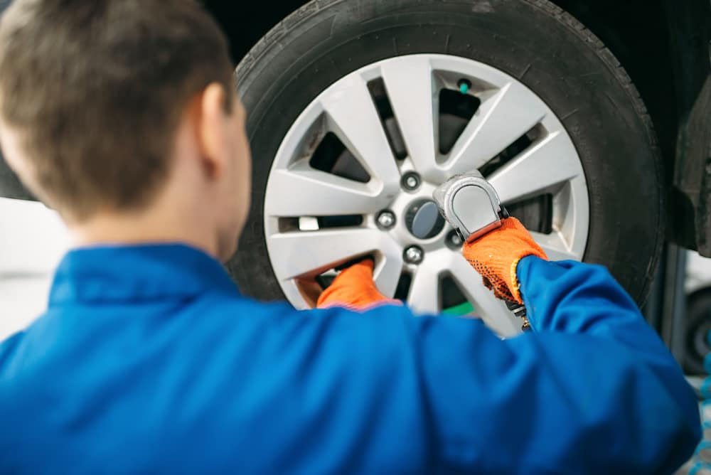 Tire Information at Hanover Nissan | Technician rotating car tire