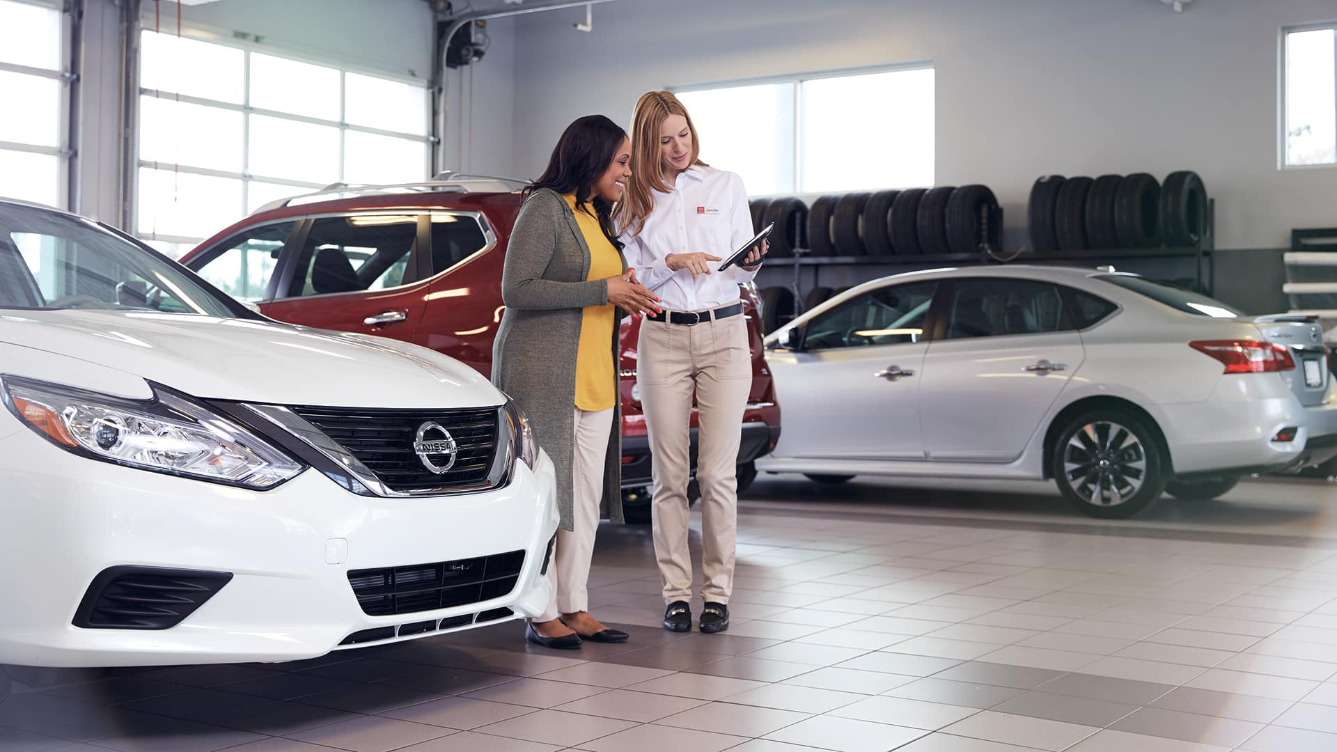 Hanover Nissan is a Car Dealership in Hanover PA near Hampstead MD | Service specialist helping woman while standing around Nissan cars