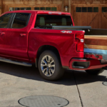 2020 chevrolet silverado 1500 red exterior with couple putting plans of wood into bed of truck