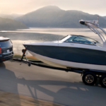 2021 chevy tahoe black exterior towing boat behind it on road with water in the backdrop