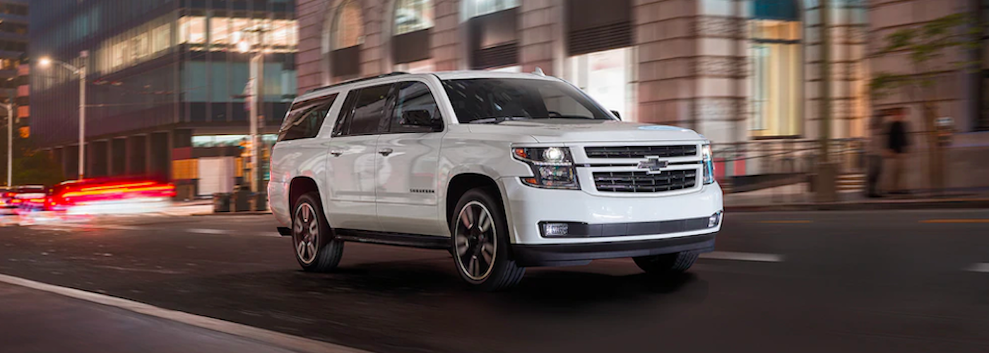 2020 chevy suburban white exterior driving on night city road