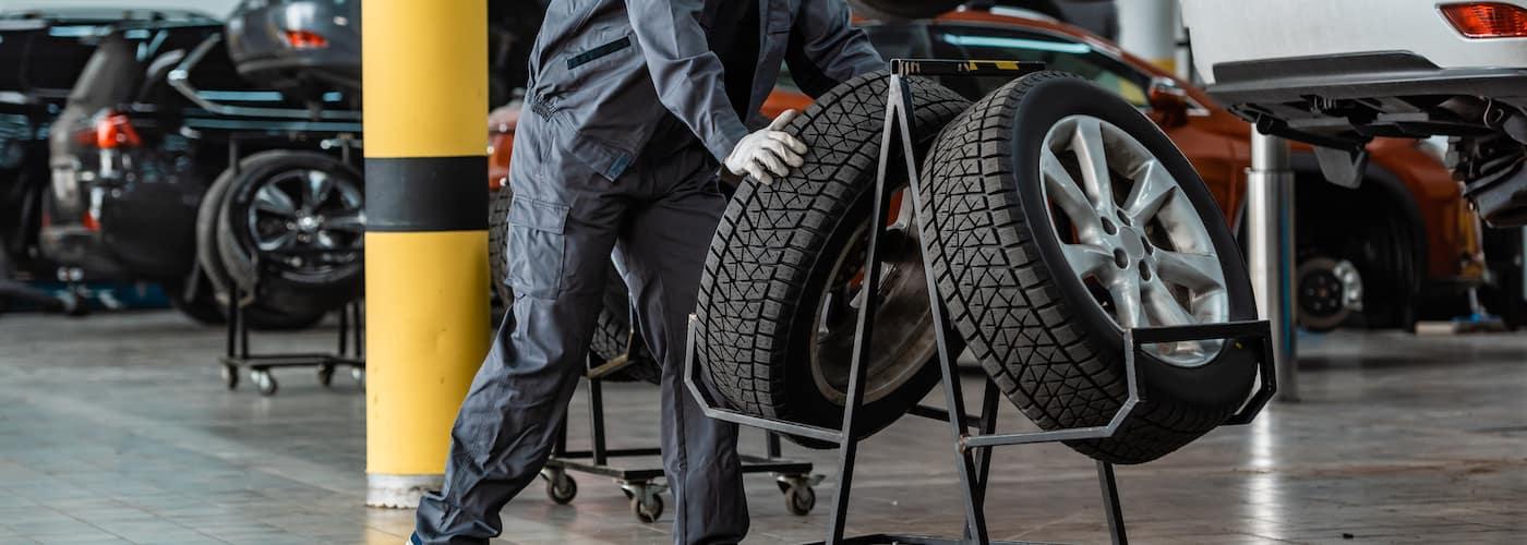 mechanic wheeling new tires in