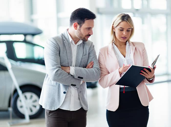 Where do I begin the process of trading in a vehicle at Jim Coleman Auto Group car dealerships in Maryland | sales agent showing man information