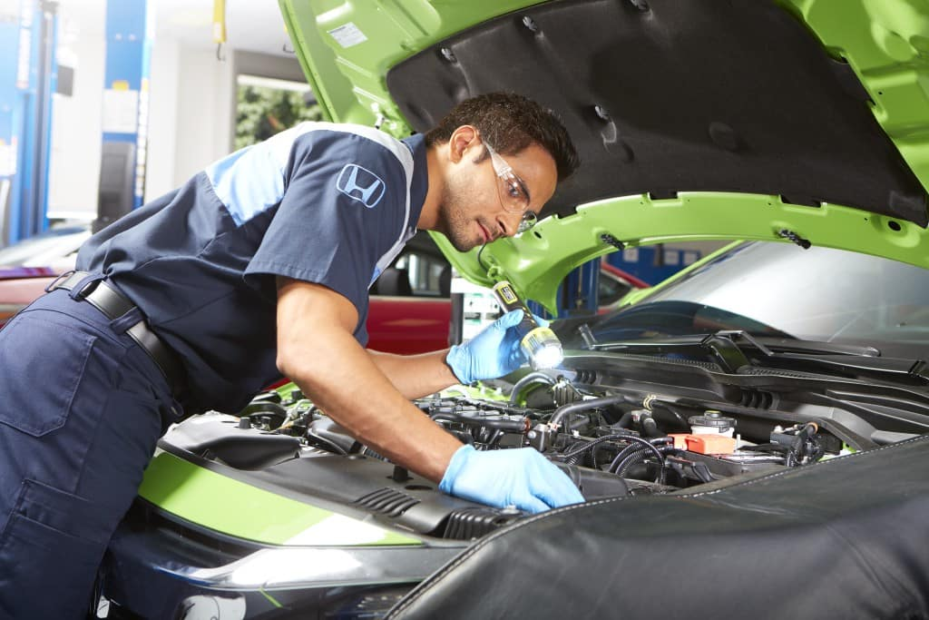 Changing your transmission fluid at Jim Coleman Auto Group of Maryland | Honda technician checking car engine