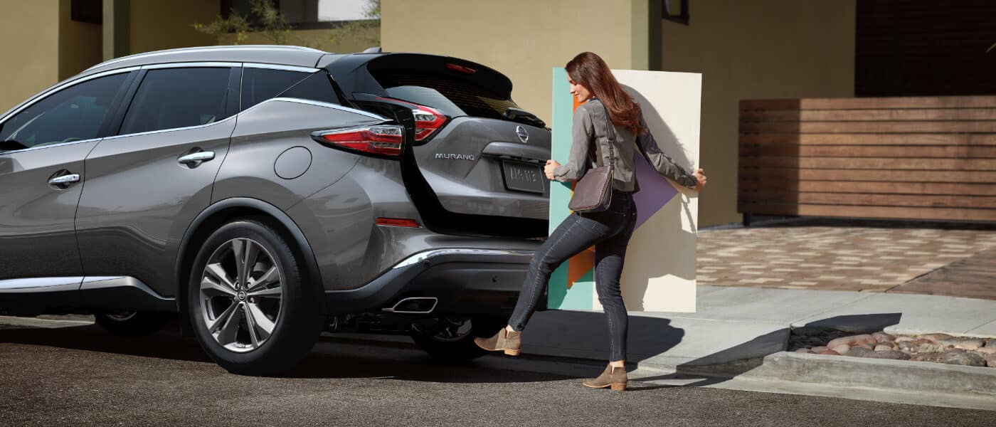 A woman putting a piece of art in the back of her Nissan Murano