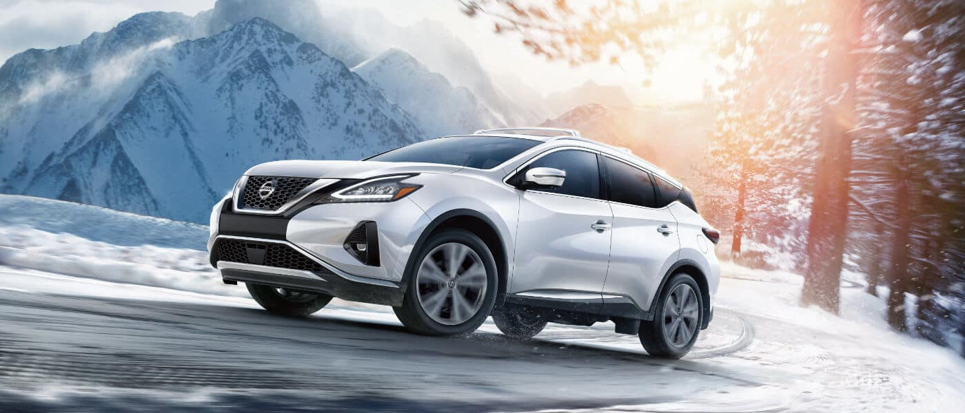 A white 2019 Nissan Murano driving through the snowy mountains
