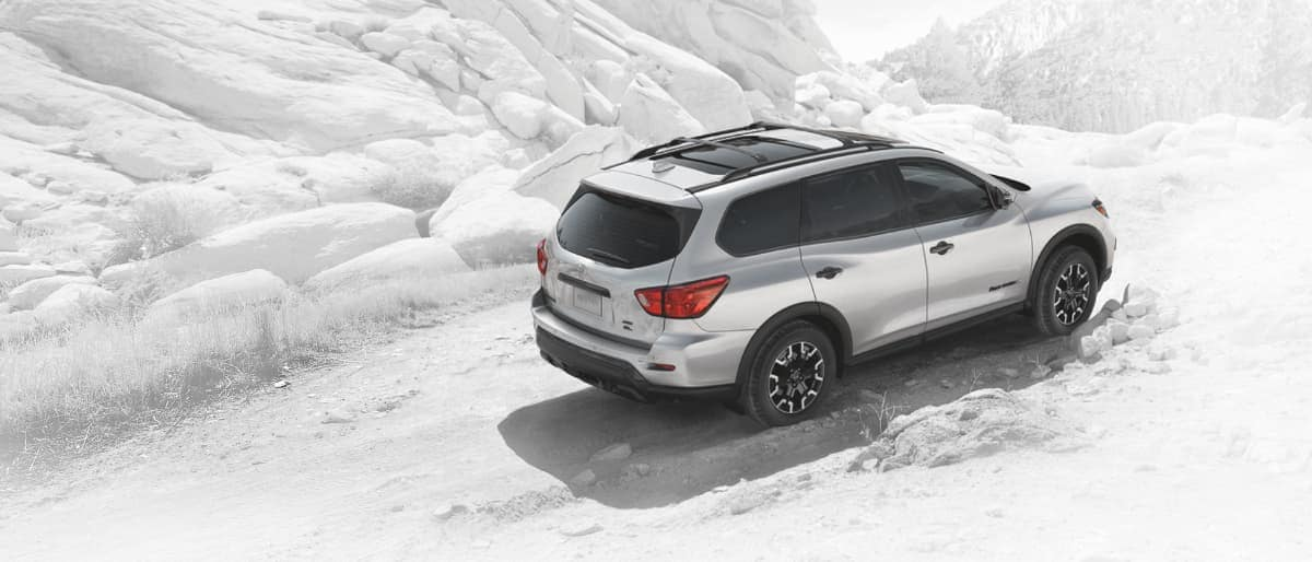 A silver 2020 Nissan Pathfinder driving through rocky terrain