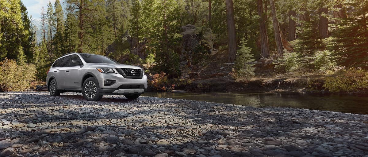 A silver 2020 Nissan Pathfinder parked by a creek