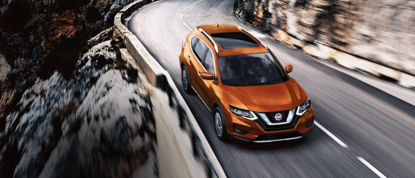An orange Nissan Rogue driving through the mountains