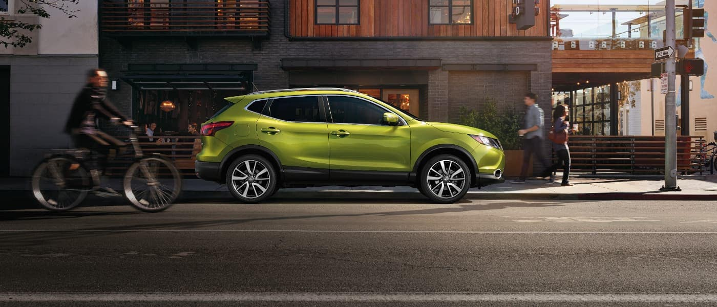 A green 2017 Nissan Rogue parked outside of a building