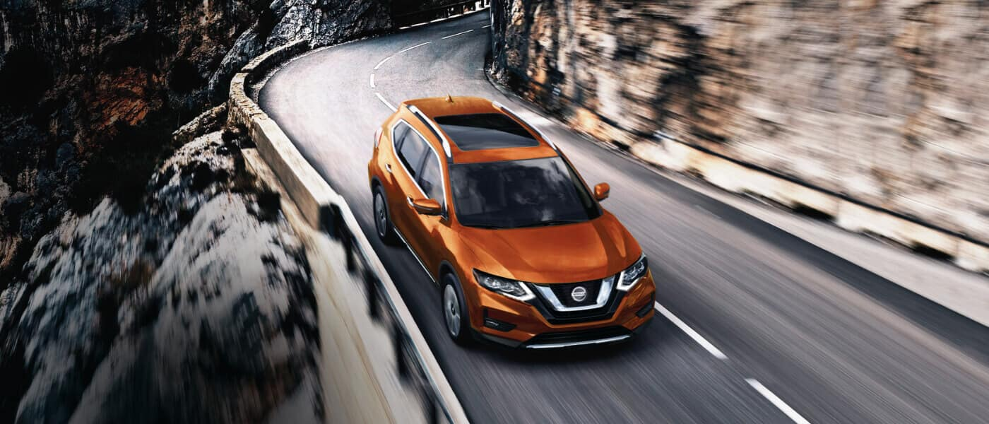 An orange 2020 Nissan Rogue driving on a mountain road
