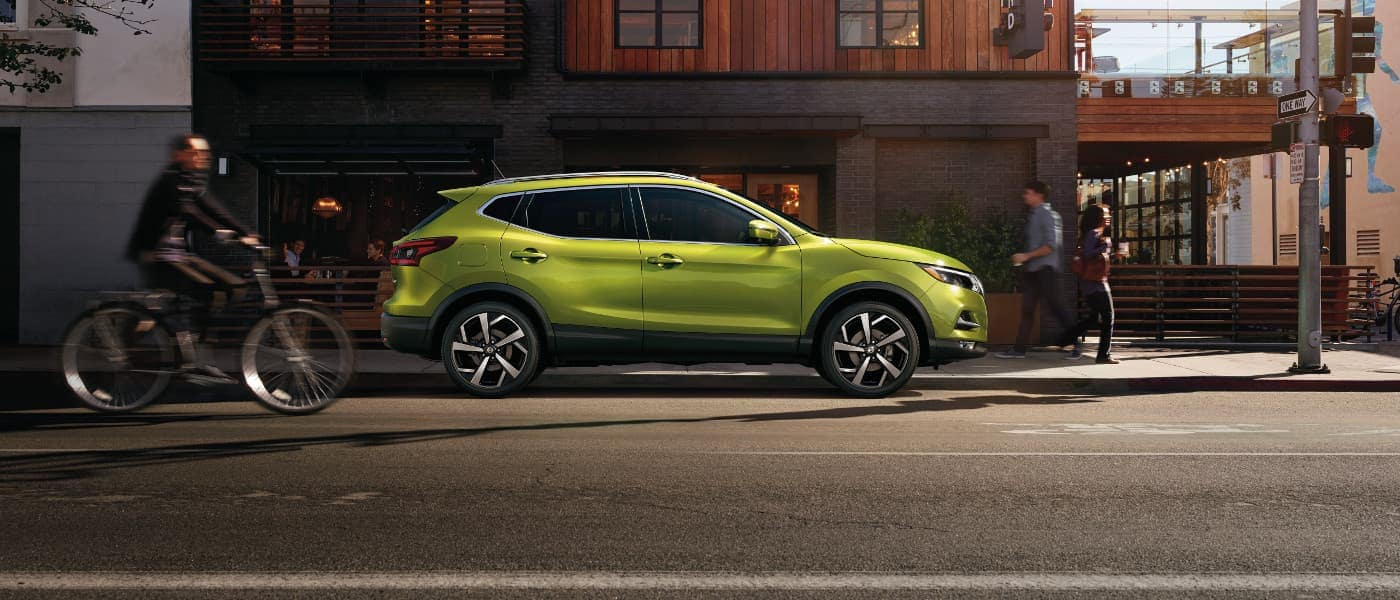 A green Nissan Rogue Sport parked outside of a building