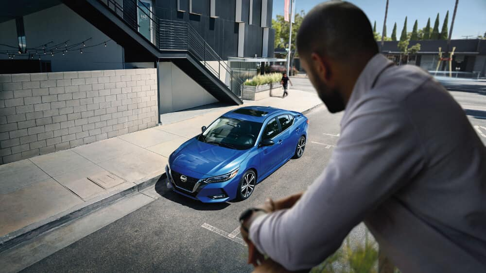 A man looking at a blue 2020 Nissan Sentra