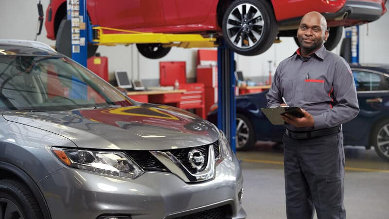 A Nissan Service technician going over a checklist on a vehicle