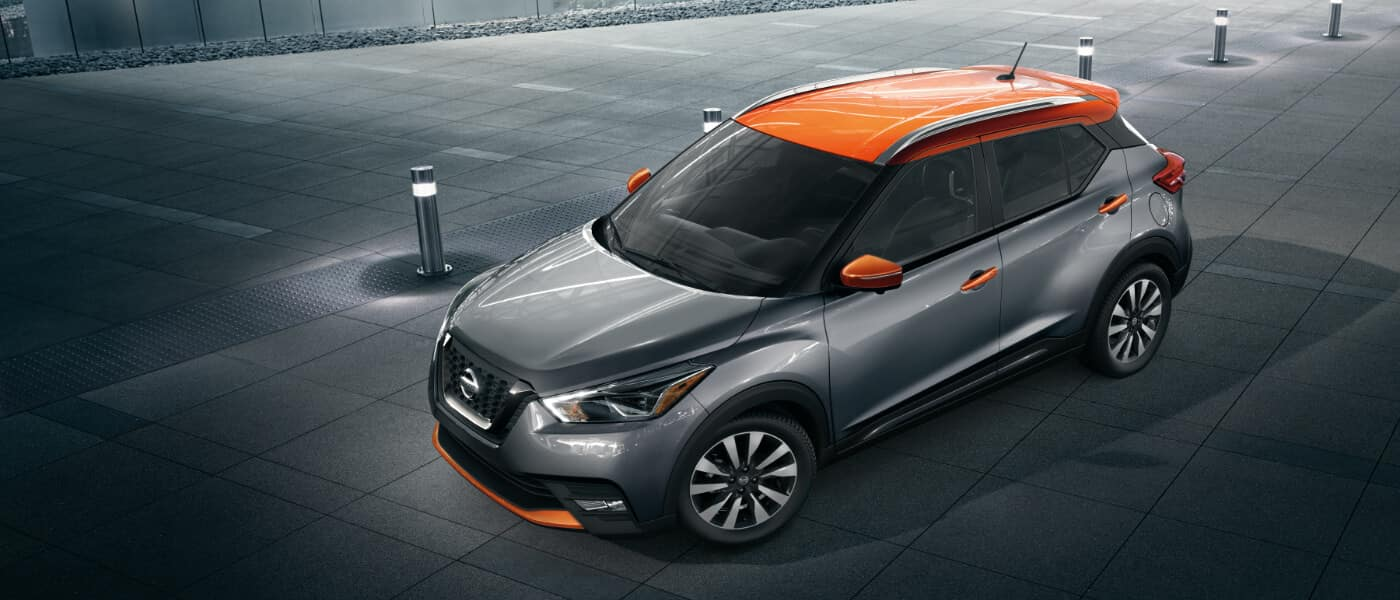 A silver 2020 Nissan Kicks with an orange roof parked next to a building