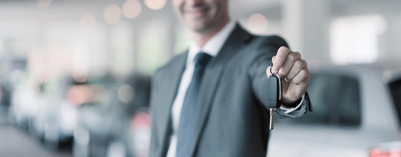luxury car salesman giving new car key
