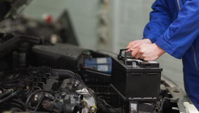 Technician removing and replacing car battery