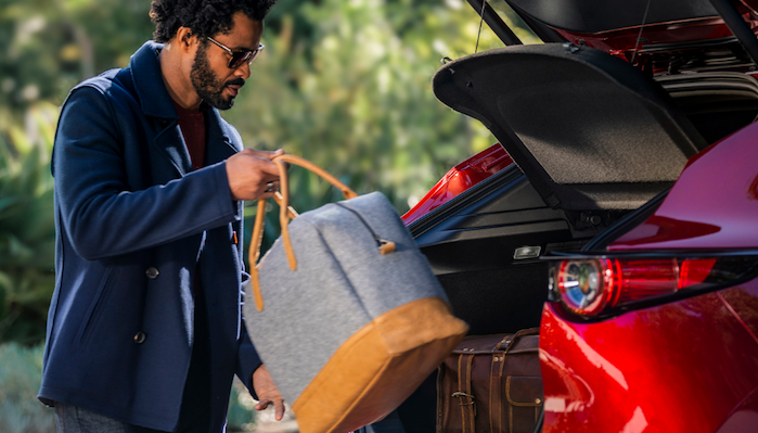 Man putting bag into back cargo area of Mazda CX-30
