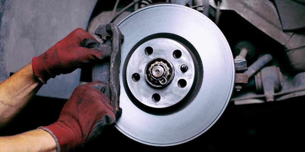 Mechanic Adjusting Brake Pad