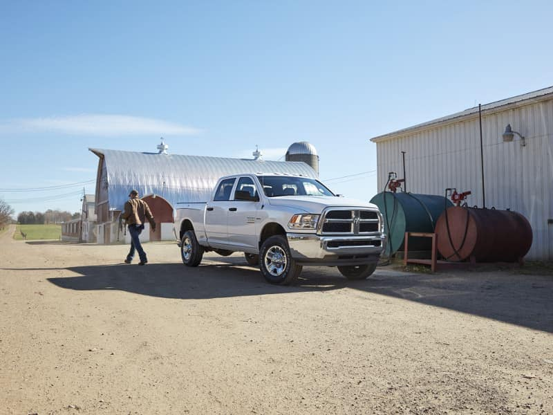 A man walking away from his white 2019 Ram 2500