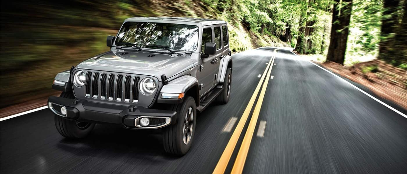 A silver Jeep Wrangler driving through a forest road