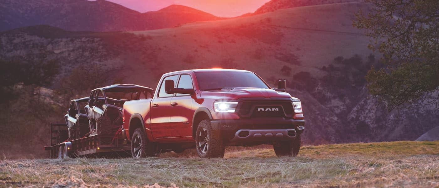 A red Ram 1500 towing ATVs through the mountains