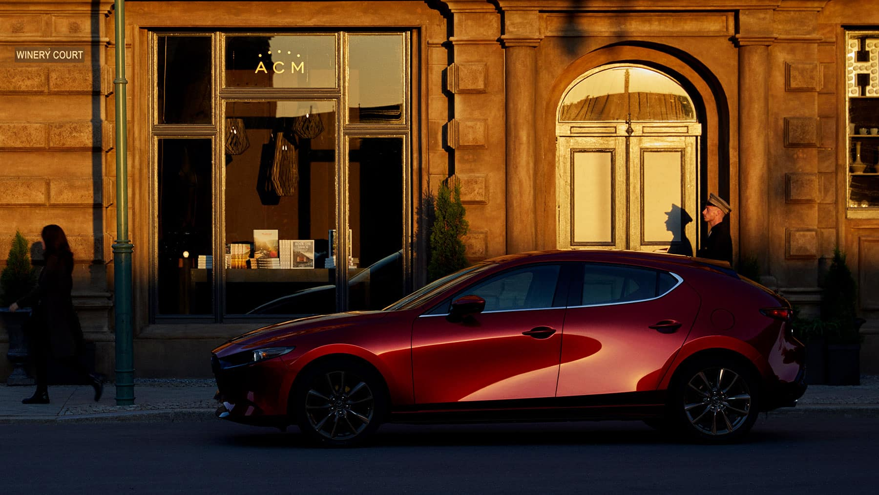 A red 2020 Mazda3 Hatchback in the golden hour against a building.