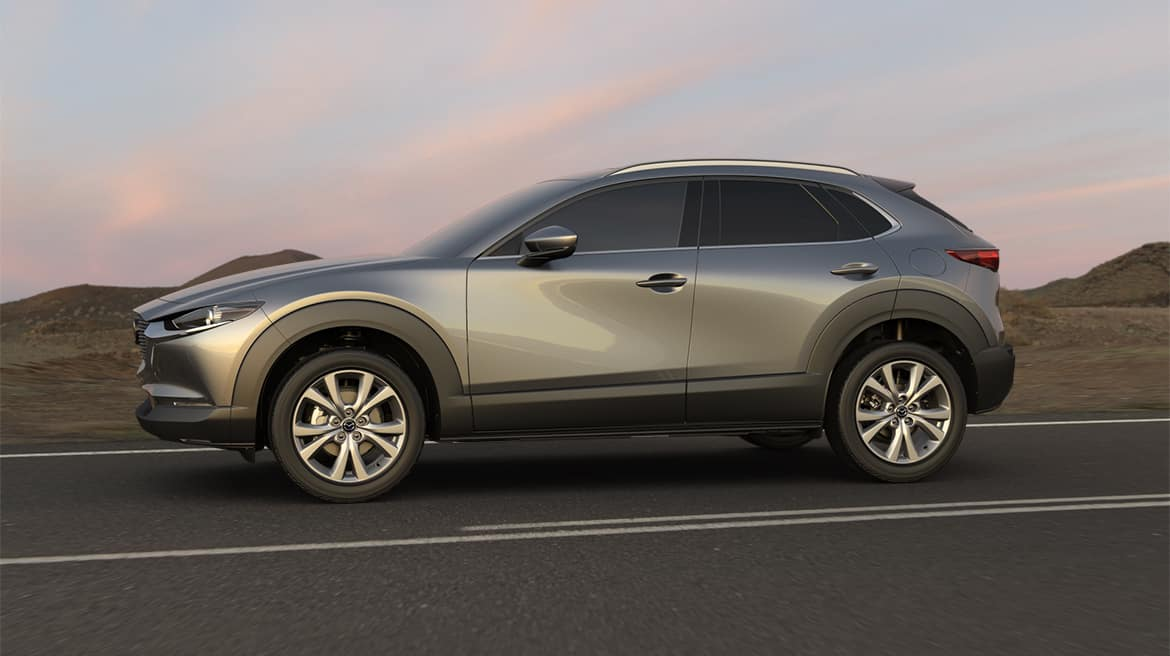 A silver Mazda CX-30 on a paved road at sunset.