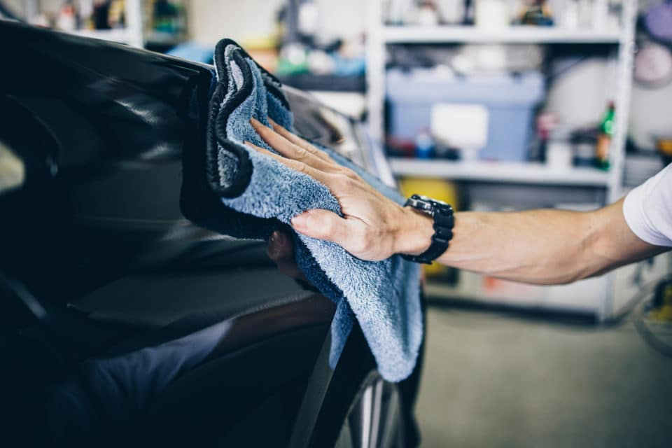 A man cleaning car with microfiber cloth