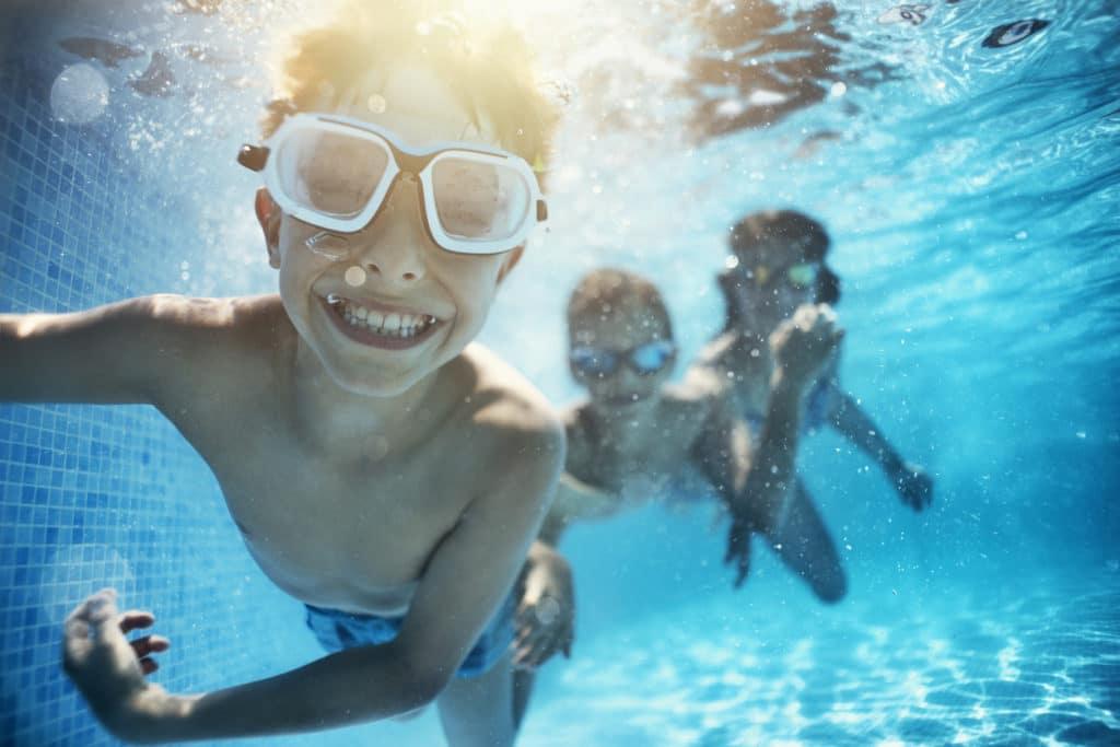 Kids playing underwater in pool