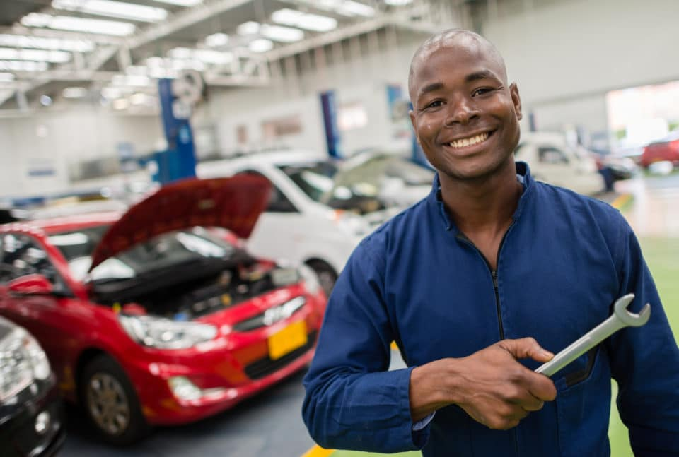 Smiling auto service technician standing in a repair shop