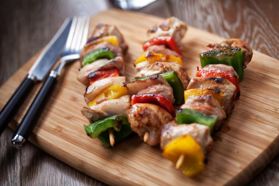 Three chicken kebabs on a wooden cutting board with a knife and fork.