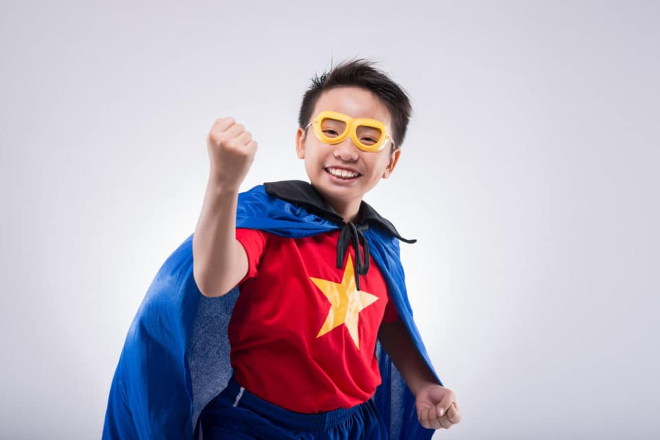 Asian boy wearing a homemade superhero costume with a cape and star logo