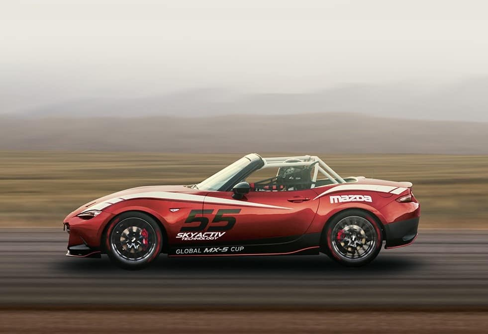 A red racing-spec Mazda Miata on the racetrack.