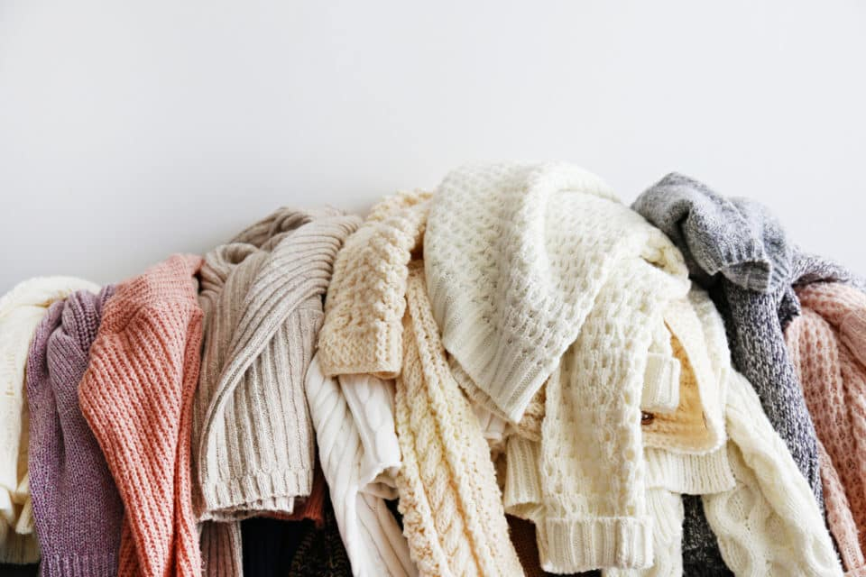 Bunch of sweaters of different material and knitting pattern in pile on gray sofa.