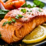 Grilled salmon on a plate with lemon slices and green garnish