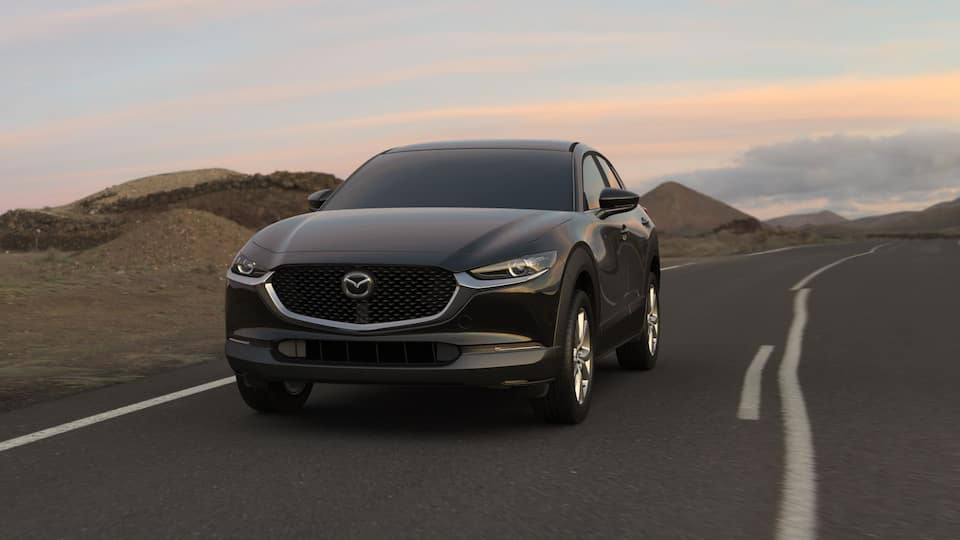 A gray 2021 Mazda CX-30 driving towards the camera on an empty road. Small mountains and a sunset in the background.