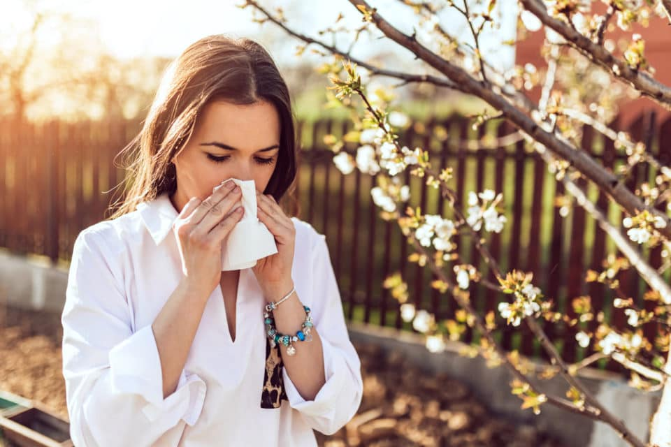 young adult woman coughing and sneezing outdoors with allergies