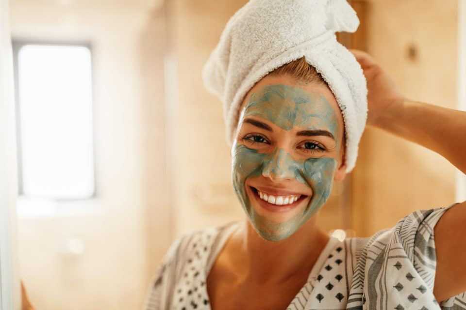 Woman standing in the bathroom with a facial mask