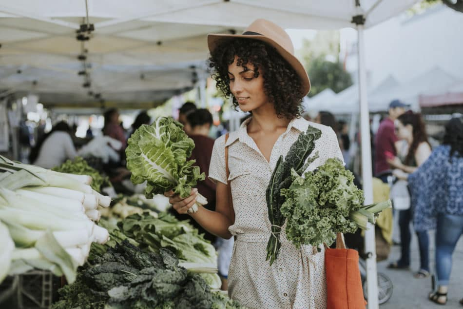 Woman buying fresh kale at farmer's market