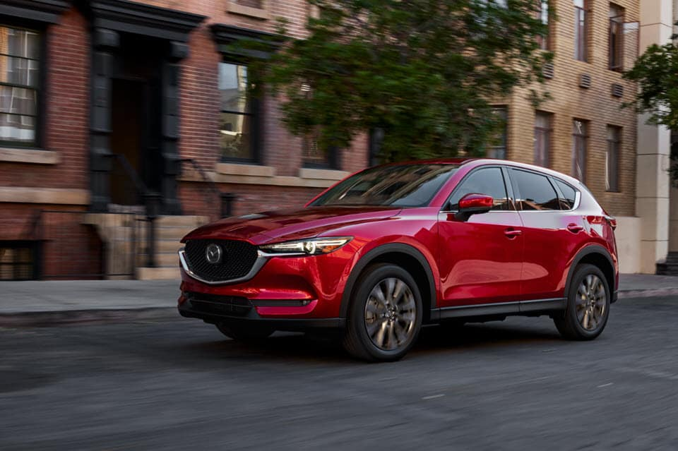 Red 2021 CX-5 on city street in front of brownstone building