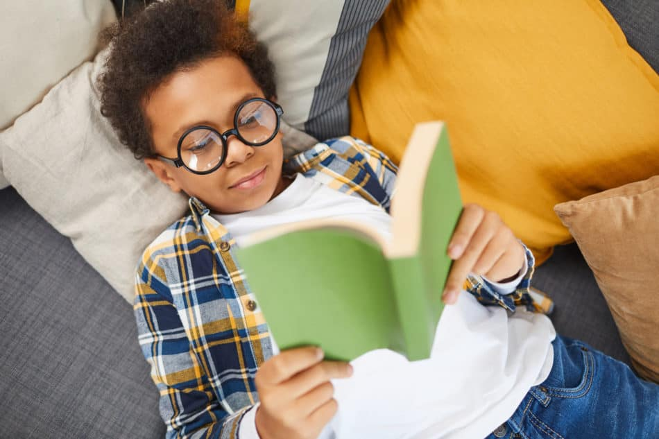 little boy wearing glasses and laying on the couch while reading a book